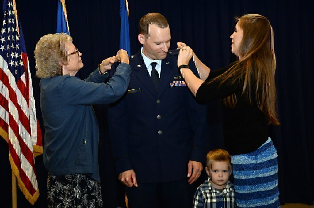 A wife helping to pin together her military husbands uniform.