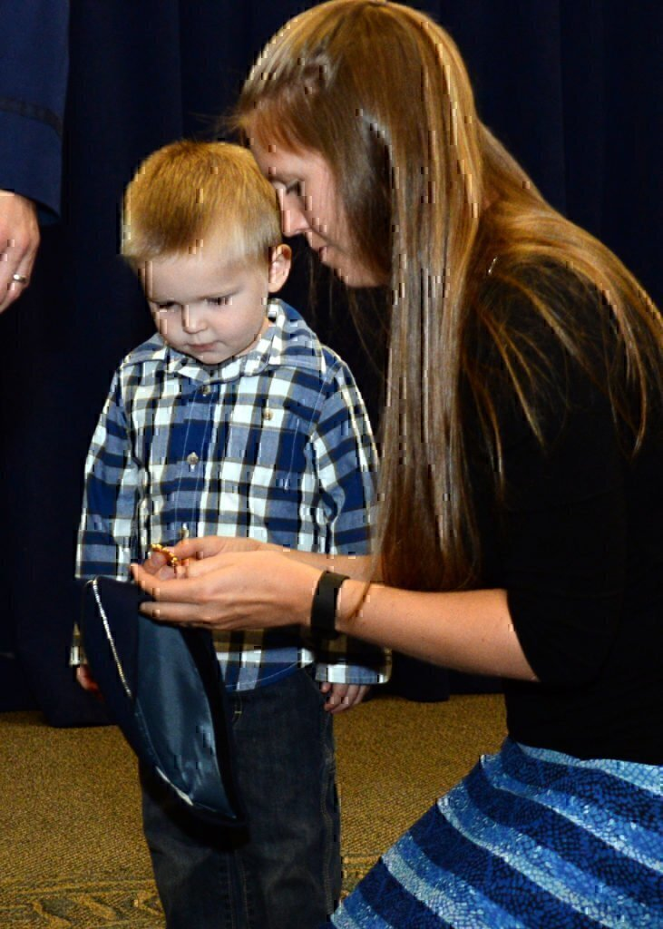 A military wife with her son looking at a badge that is going to be placed on her husbands uniform.