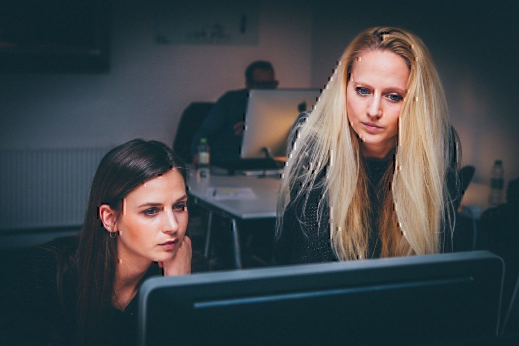 Two women leaning over a computer during their work day.