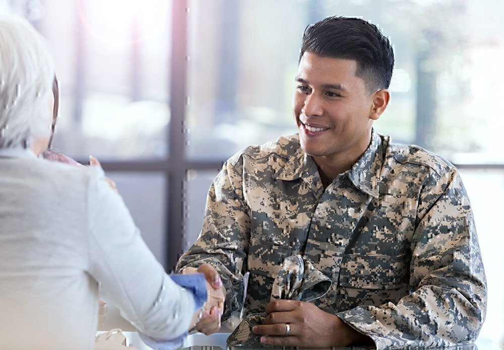 Service member shaking the hand of a training leader.