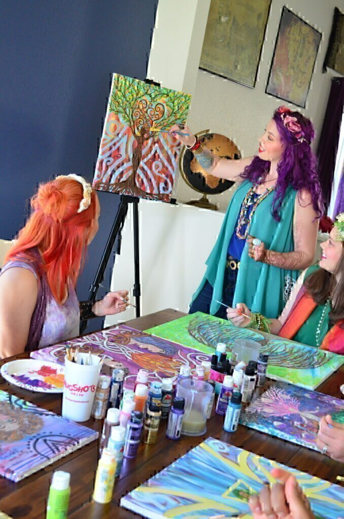 A groups of women using bright, beautiful colors to paint an amazing picture.