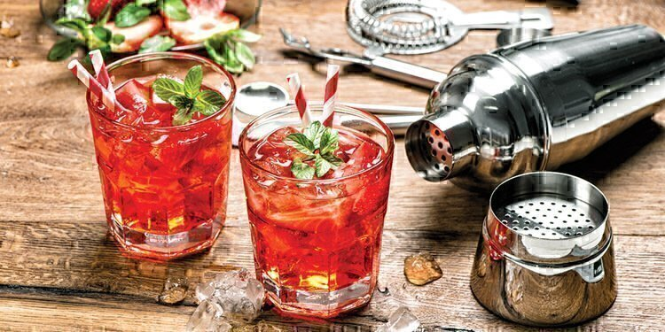 Two strawberry cocktails at the fore-front with the ingredients and shaker in the background.