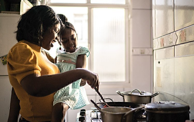 A mother holding her daughter while stirring dinner together.