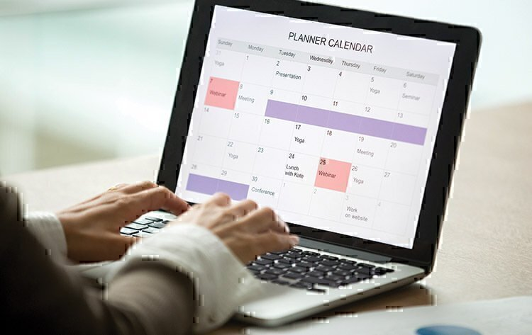 A women using her laptop to set up her calendar for her month.