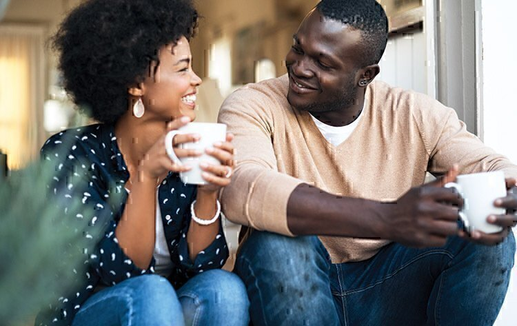 A married man and women smiling each other while drinking coffee.