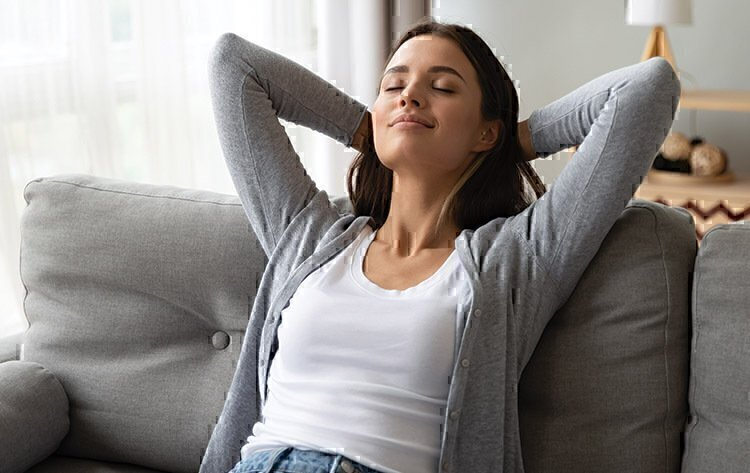 A women seated on a couch, relaxing.