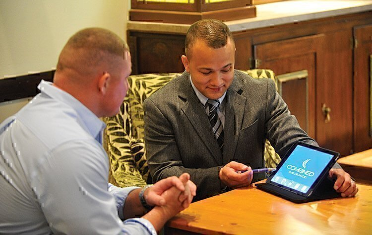 An insurance agent showing a customer the benefits of their service.