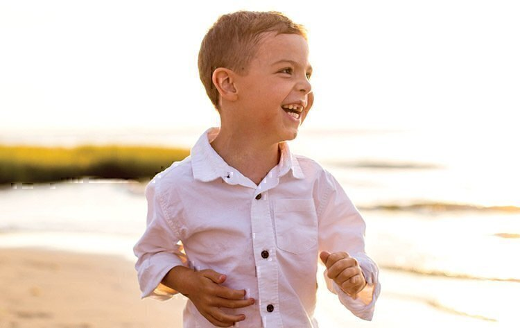 Tyler Benscoter running down the beach while smiling and laughing.