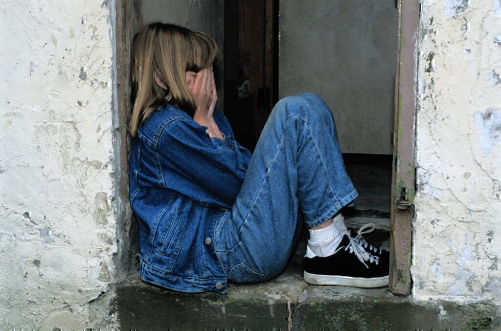 A young child sitting in a doorway while holding her face in her hands while crying.